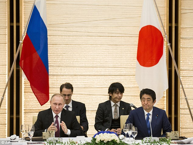 Vladimir Putin (left) was named this week by Forbes as the world's most powerful person. He is in Tokyo today for talks with Prime Minister Shinzo Abe (right)