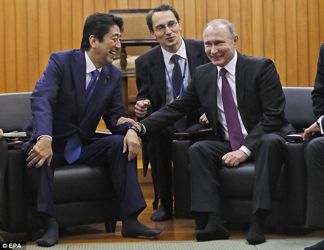 Vladimir Putin (right) is in Tokyo today meeting Japan's Prime Minister Shinzo Abe (left). The pair laughed and joked during a visit to a judo hall