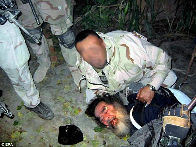Former Iraqi leader Saddam Hussein moments after his capture by US forces
