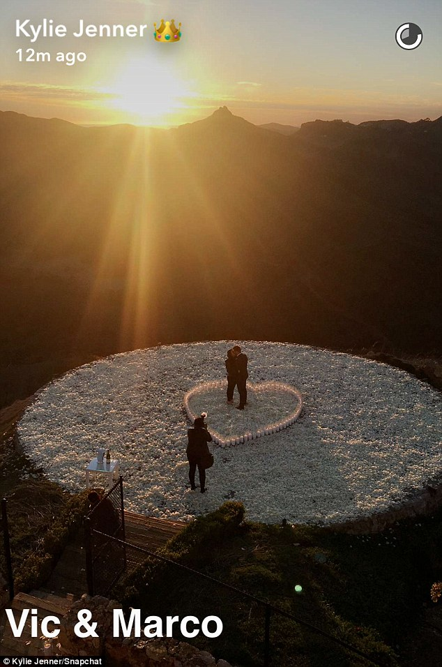 She said yes! The romantic proposal took place on a hilltop decorated with a heart-shaped arrangement of candles, with cheering loved ones looking on
