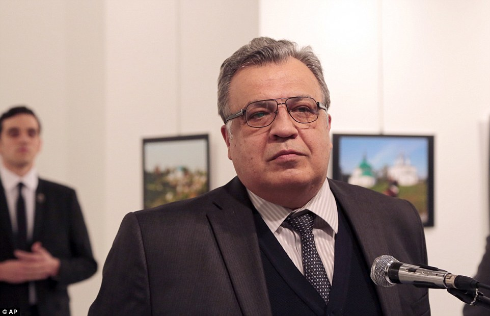 The gunman (left, in the background) was seen standing behind Andrei Karlov, 62, main, moments before he opened fire