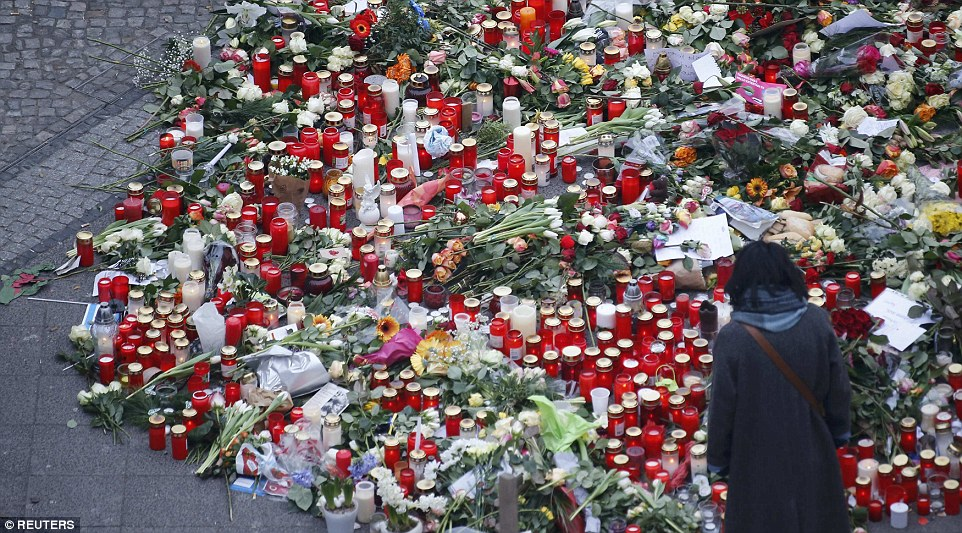 Mourners placed flowers and candles at the site while German flags flew at half-mast and Berlin's landmark Brandenburg Gate was lit in the national colours in honour of the victims
