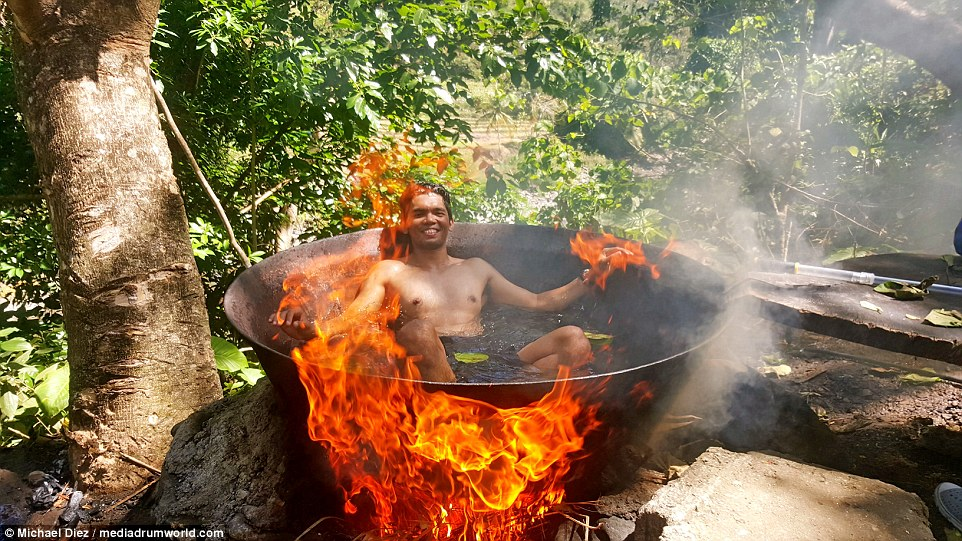 Michael bathes in the tub as the flames make the water boil. The baths are one of the prime attractions for visitors of Tibiao