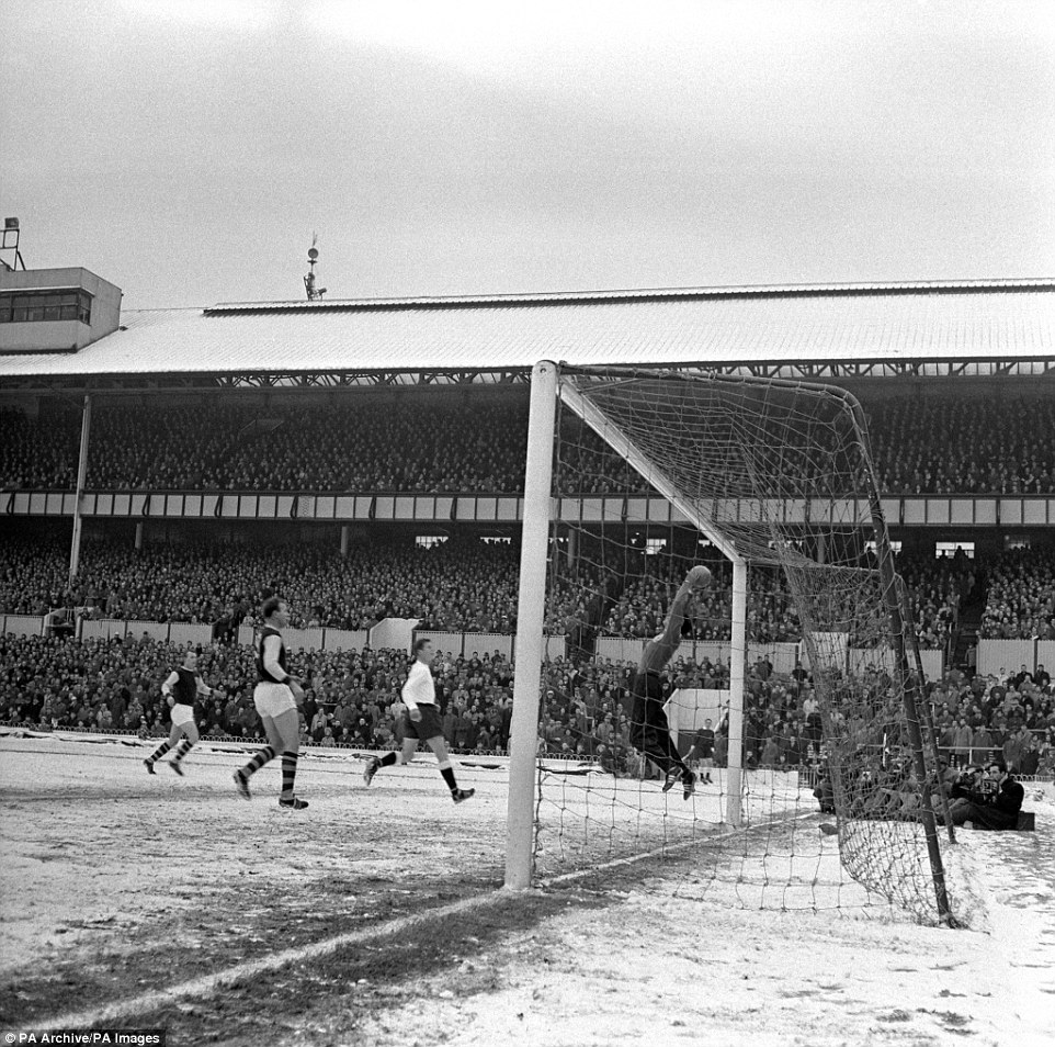 Tottenham goalkeeper Bill Brown, wearing a tracksuit in the cold, makes a save from Burnley centre-forward Andy Lochhead