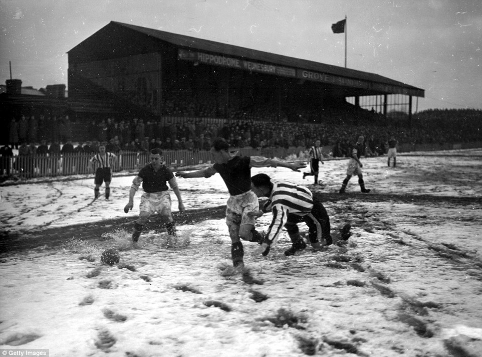 One footballer takes a tumble in this 1938 game between two unknown teams as the snow begins to turn to slush