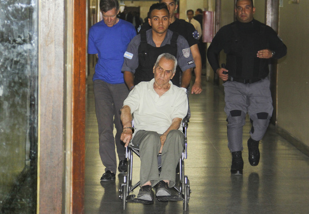 Handcuffed to a wheelchair, priest Nicola Corradi and the Rev. Horacio Corbacho, left, are escorted to a courtroom in Argentina. They are accused of sexually abusing children at a school for deaf youngsters