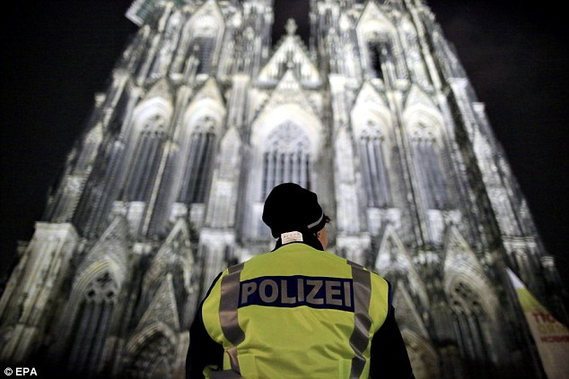 A police officer stands in front of the Cologne Cathedral on Christmas Eve. This year the city will not be sub-contracting out security but will be relying on 1,500 ordinary police officers