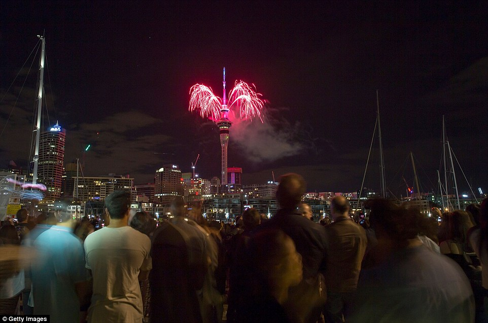 Crowds are pictured gathered to watch the SkyTower firework display during New Year's Eve celebrations in Auckland