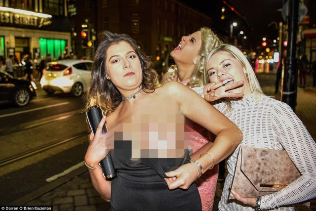 A party-goer flashes her breast in Sheffield as millions of Britons brought in the New Year by drinking to excess