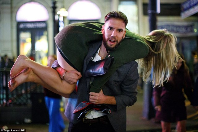 A reveller gives a helping hand to a female companion during the wild New Year celebrations in central London