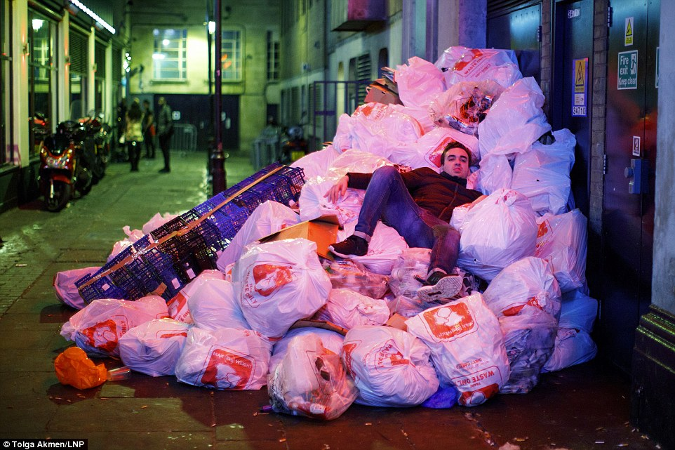 One man was seen lying in a heap of rubbish bags with filthy trousers in London during the booze-fuelled celebrations