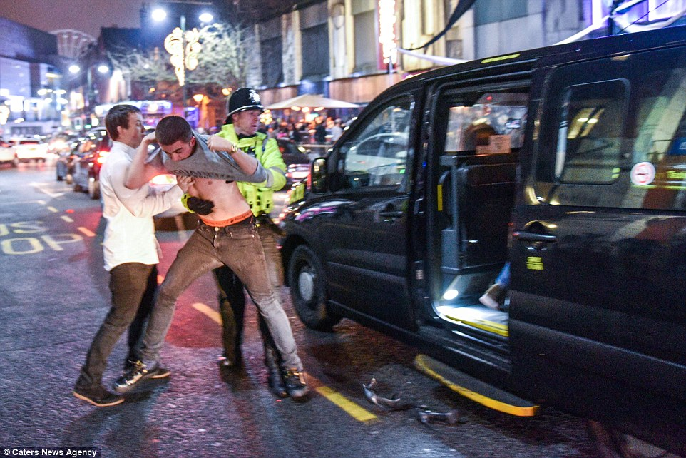 A police officer ejects a reveller from a taxi after he attempted to skip the queue on one of the busiest nights of the year