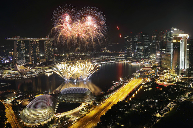 Fireworks explode above Singapore's financial district at the stroke of midnight to mark the New Year's celebrations on Sunday, Jan. 1, 2017, in Singapore. (...