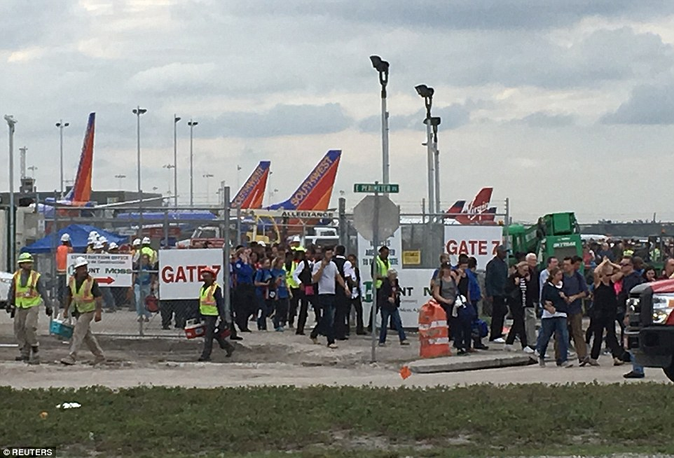 Travelers and airport workers are evacuated out of the terminal after airport shooting at Fort Lauderdale-Hollywood International Airport in Florida