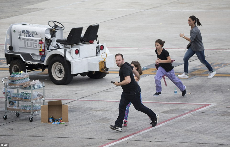People are seen desperately running across the tarmac after the shooting earlier in the afternoon