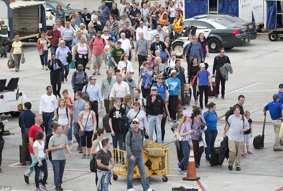 Passengers are hurried onto the tarmac during the evacuation after the gunman opened fire