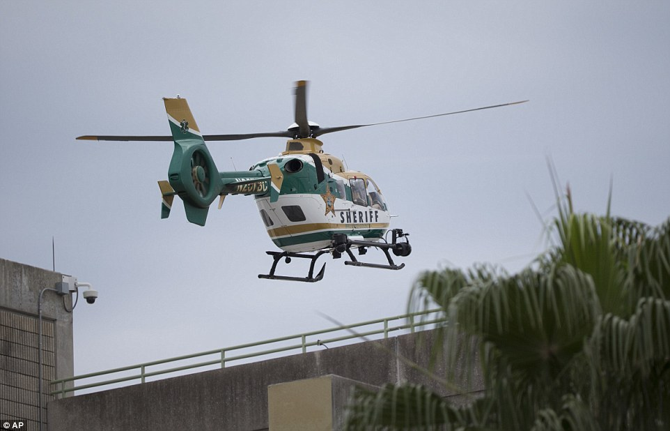 A law enforcement helicopter is seen flying over a garage at the airport after it was put into lockdown