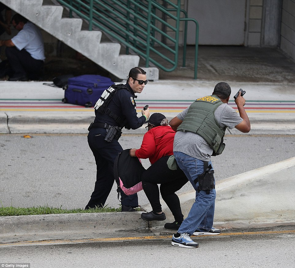 Police assist a woman seeking cover outside Terminal 2 at the Florida airport on Friday