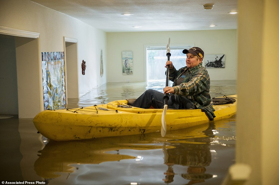 Drought-busting series of storms began to move out of the region after days of heavy rain and snow that toppled trees and wreaked havoc as far north as Portland, Oregon. Lorin Doeleman uses a kayak to check her flooded home on Wednesday, January 11 in Guerneville, California. She is moving her belongings to her Sacramento home