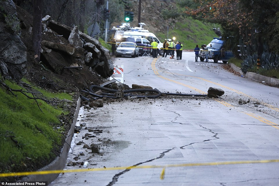 Torrents of rain gushed down the street even after rescuers finished evacuating residents more than seven hours later. A slab of concrete rests in the road after it slid down a rain-soaked hillside in the Hollywood Hills neighborhood
