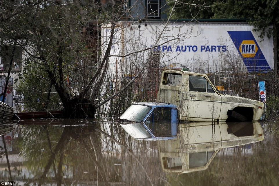 Trucks sit partially immersed in floodwater along River Road in Guerneville, California