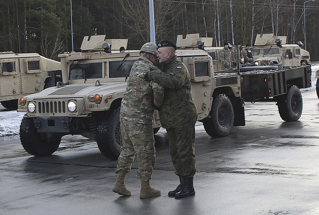 A US soldier (left) is welcomed by a Polish army official as US Army vehicles cross the Polish border in Olszyna, Poland