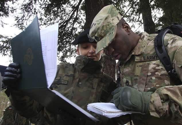 An American (right) and a Polish soldier (left) check documents in Zagan, Poland, on Thursday