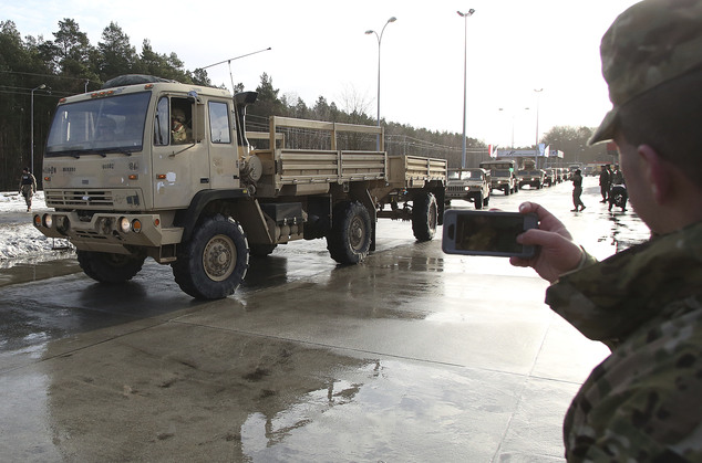 An unidentified soldier uses an iPhone to snap photos of a convoy of military vehicles rolling into Poland on Thursday