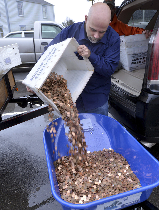 Nick Stafford fills one of five wheelbarrows full of change, mostly pennies, at the DMV in Lebanon. Stafford was paying the sales tax on two cars that he was titling