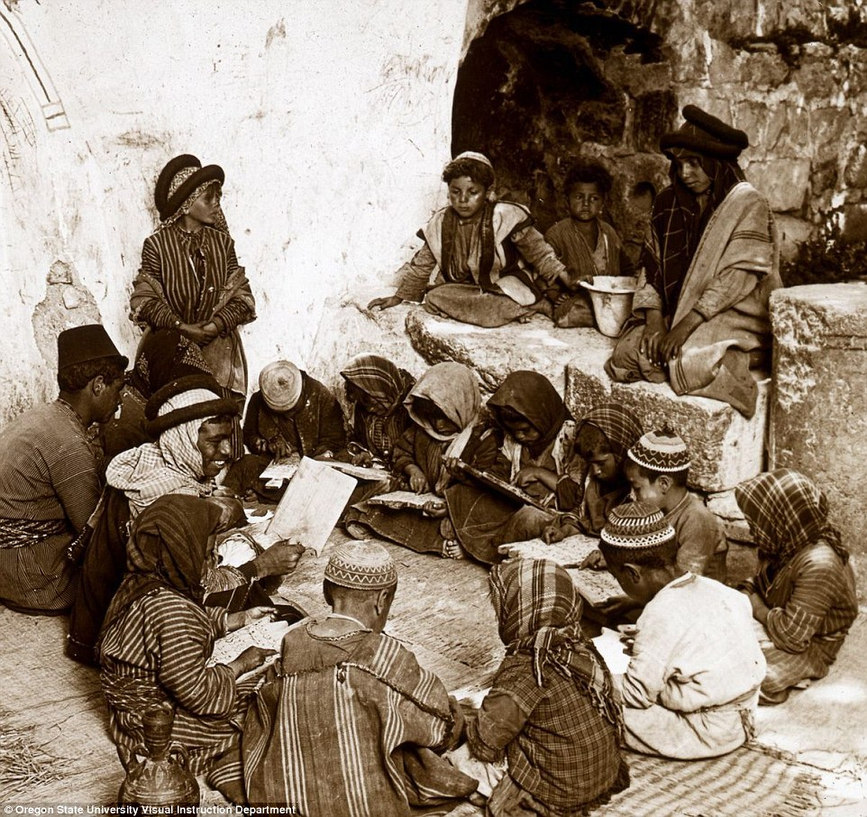 A Muslim school in Ramah, where a teacher, with a page of the Koran in his hand, reads to young pupils seated in a circle