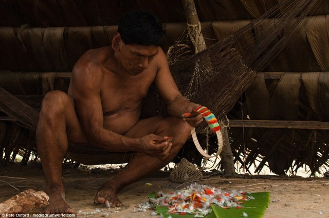 Un hombre construye un collar de plumas de aves. La tribu de hacer algo de dinero con la venta de artesanías a los turistas