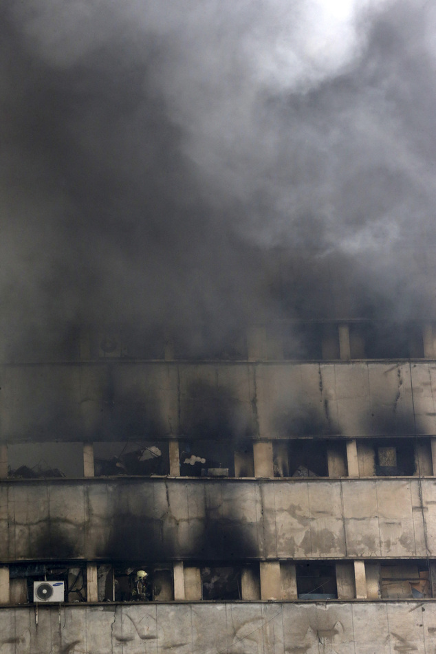 An Iranian firefighter, bottom left, works in operations to extinguish fire of the Plasco building in central Tehran, Iran, Thursday, Jan. 19, 2017. The high...