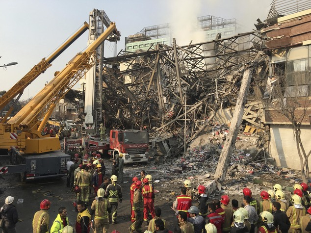 Iranian firefighters work at the scene of the collapsed Plasco building after being engulfed by a fire, in central Tehran, Iran, Thursday, Jan. 19, 2017. A h...