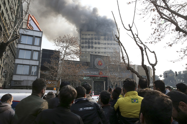 Iranians watch the Plasco building where smoke rises from its windows in central Tehran, Iran, Thursday, Jan. 19, 2017. The high-rise building engulfed by a ...