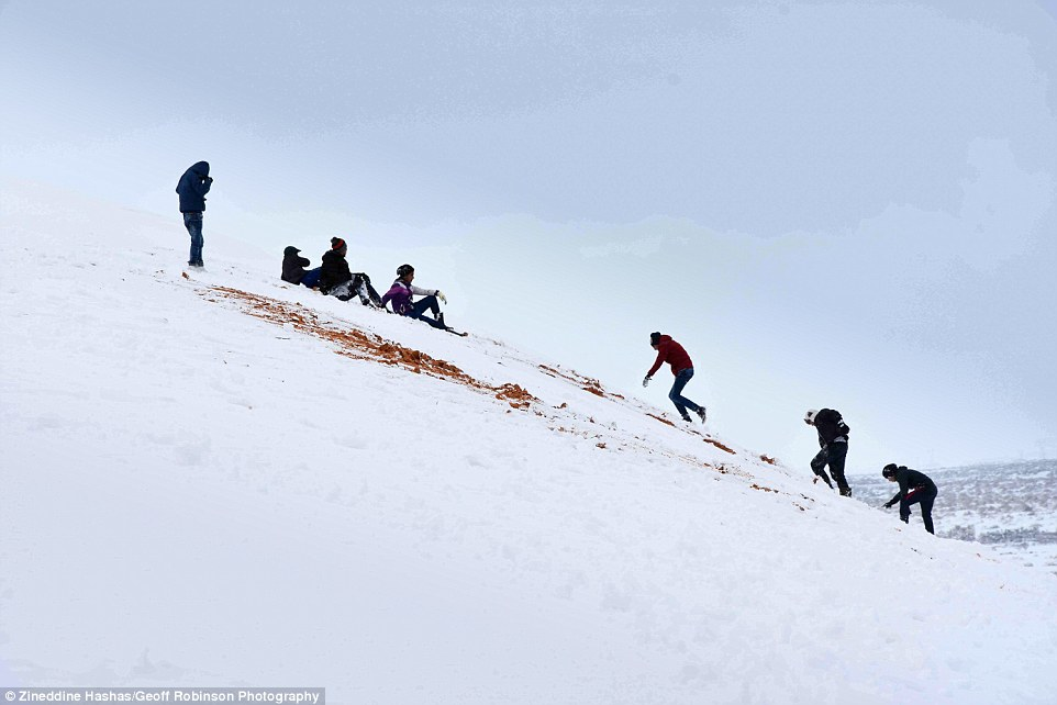 Children played in the snow on the dunes above the town of Ain Sefra for the first time in their lives today (pictured)