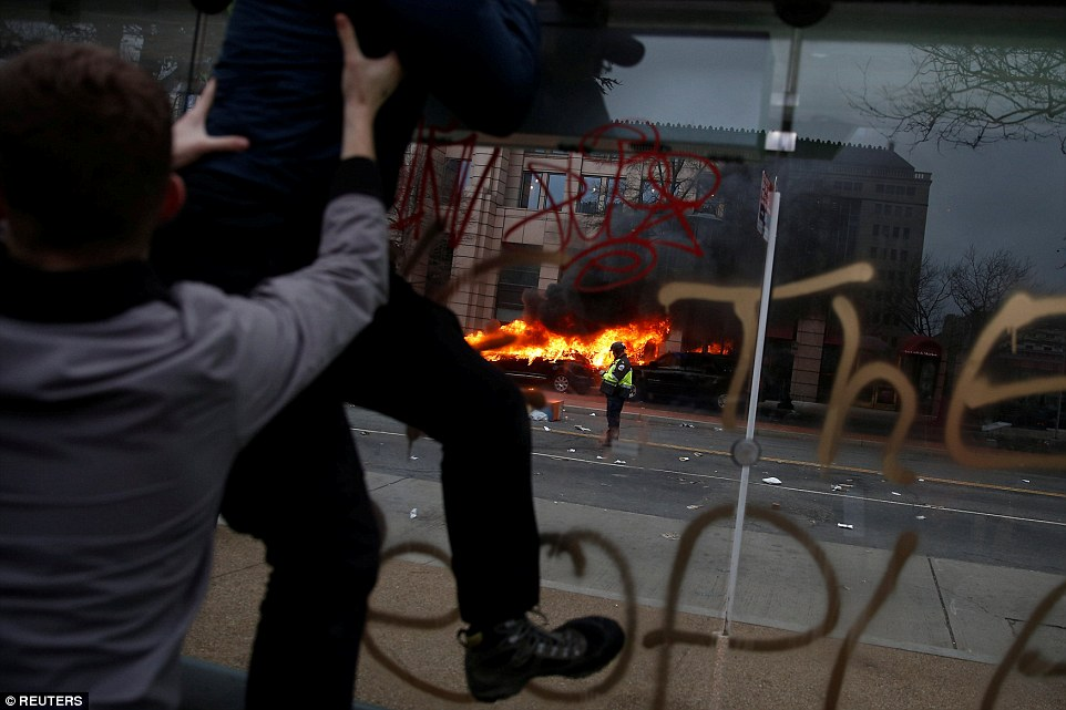 Activists leave the site of a limousine which was set ablaze during a protest against Trump. Someone wrote on the side of the burning limo: 'We the People'
