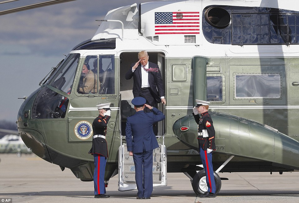 President Trump is pictured above saluting as he gets off Marine One at Joint Base Andrews