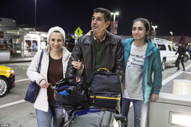 Radgoudarzi (center) made his way through the arrival pick up area with his wife Susan (left) and daughter Niloofar (right) after being detained  at San Francisco's SFO International Airport as a result of Trump's order