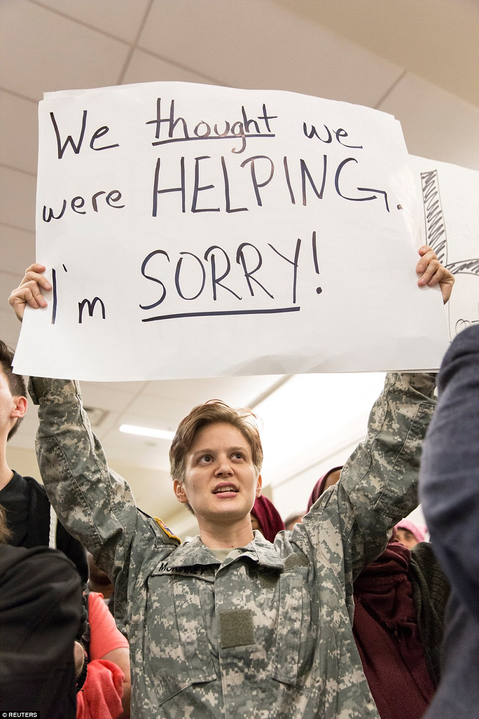 A female veteran held a sign reading 'We thought we were helping, sorry' at Dallas/Fort Worth International Airport