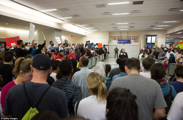 Demonstrators gathered in the international arrivals area at Dallas-Fort Worth International Airport to protest on Saturday
