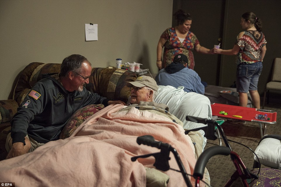 Comfort:Chris Arden (left) keep evacuee George Moody company in the main sanctuary of the Neighborhood Church of Chico in Chico