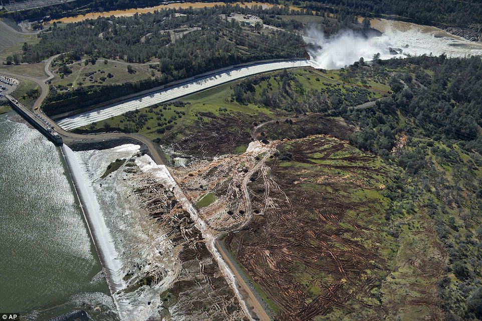 Aerial: Lake water flows over the emergency spillway, bottom left, at Lake Oroville for the first time in the nearly 50-year history of the dam on Saturday