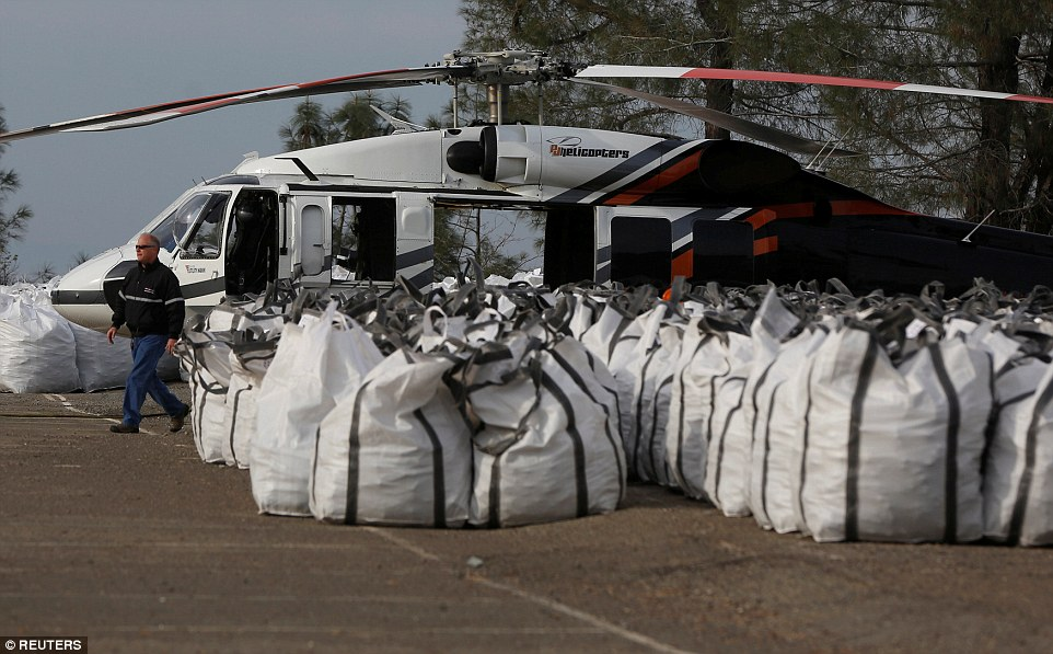 Effort: Officials said the situation seemed less dire overnight but Sacramento television station KCRA reported that helicopters from around the state were sent to drop chest-high bags of rocks to close the hole in the spillway