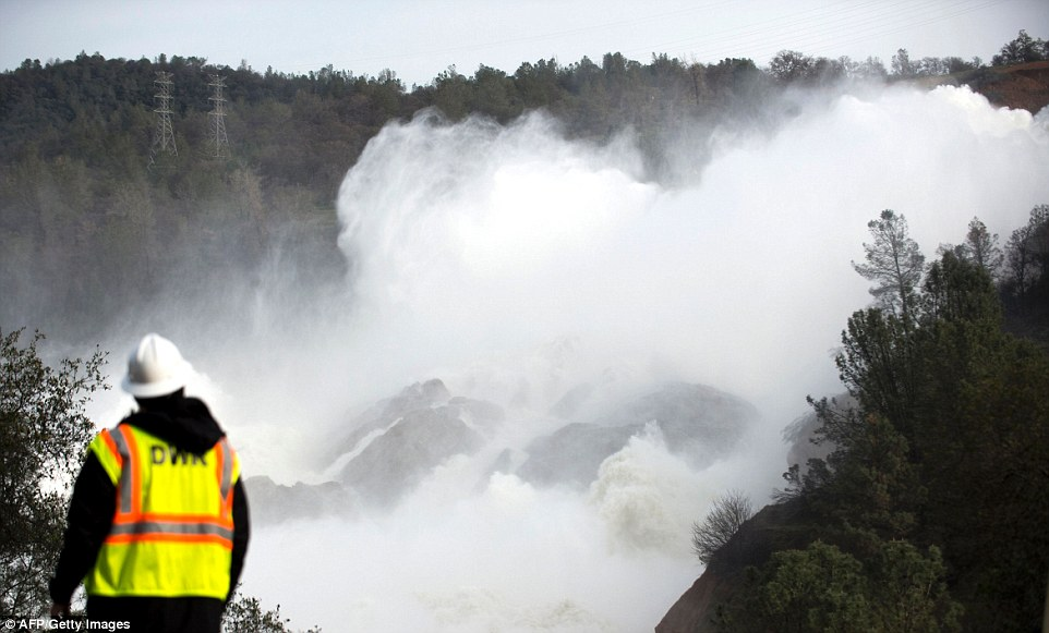 Power: A water utility worker stares at the staggering amount of water being released down the main spillway at the Oroville Dam after its spillway almost collapsed on Sunday - sparking the evacuation of 200,000 people