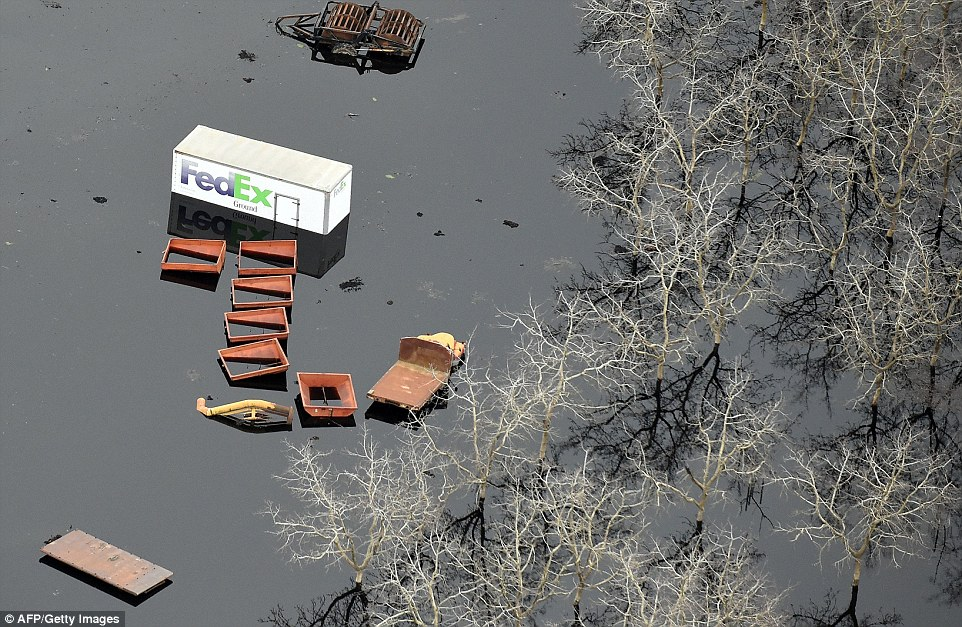 Going nowhere: Vehicles and carts are seen trapped in the swamp - for how long remains to be seen. Officials responded to the 2005 request for spillway reinforcements by saying there was no risk of this kind of flooding