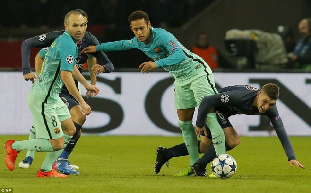Marco Verratti (right) falls while challenged by Barcelona's Neymar as Andres Iniesta looks on during the early stages