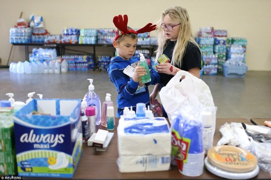 Displaced children pick up supplies of soap and toys at the center in Placer County. They have been told they can go home but that the situation may change