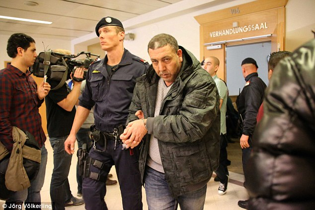 One of the suspects, Sabah Al-J., is brought into the courtroom in handcuffs