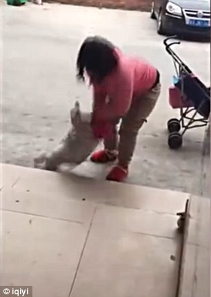 The footage, captured in the Guangdong province of southeast China, shows the woman yelling at the crying infant as she beats her with her foot against a tiled floor