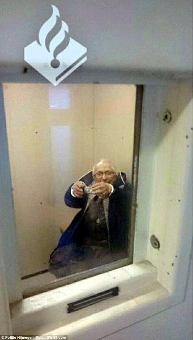 The grandmother proudly holds out her arms showing the handcuffs from behind the cell door